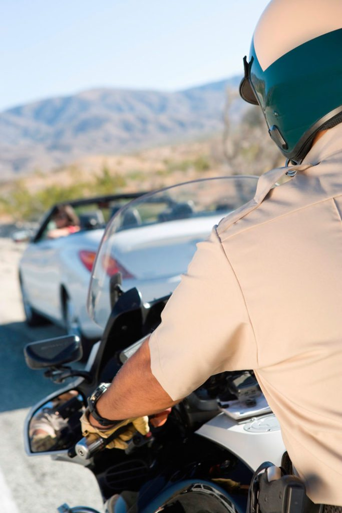 The idea of misdemeanor criminal defense is illustrated with a photo of a police officer pulling over a car.