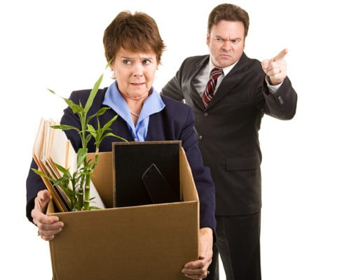 Fired corporate employee holding her belongings in a cardboard box, as her boss orders her out of the building.